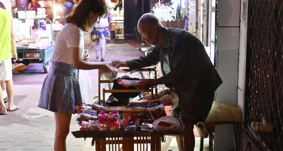 107岁老人大学门口卖鞋垫 有人买完再悄悄放回
