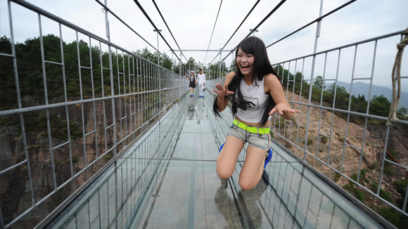 美女在玻璃桥上走着,突然桥面开裂了