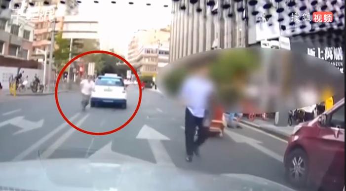 车胎被踢惹恼的哥 竟将车停路中央背后飞踹路人